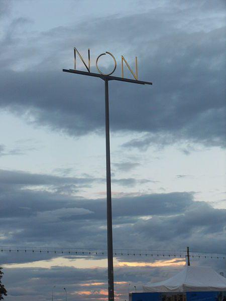 Markus Raetz: OUI/NON (2000) – Place du Rhône, Genève. Sculpture anamorphique, mât en acier galvanisé recouvert de peinture micacée, surmonté de deux traverses en acier sablé, hauteur 10.45 m (don.: Fondation Hélène et Victor Barbour, Genève)