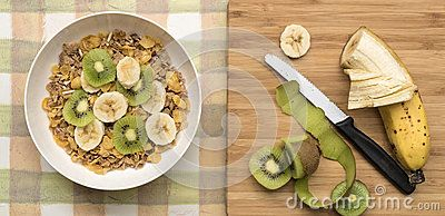 A white bowl of multi grain breakfast cereal topped with slices of  kiwi fruit and banana beside a cutting board and knife.