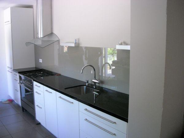 Achterwand in keuken van gelakt grijs glas.