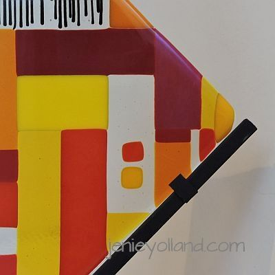 TEST PATTERN sculptural glass stands in a wrought iron v shaped stand.  Orange, ruby red and yellow by jenie yolland