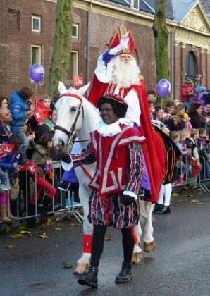 Sint komt aan in Amsterdam bij 't Scheepvaartmuseum, daar start de intocht door de stad. Piet en Sint wuivend te paard.