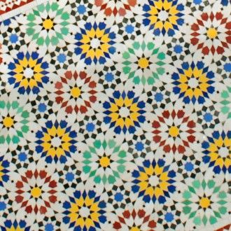 """Hier sehen Sie die Detailaufnahme der Tischplatte von unserem Gartentisch aus Marokko """"Ankabut"""" Oval. Die einzelnen von Hand geschlagenen Fliesen wurden in kunstvollen Mustern in Beton gebettet und von einem Eisenring ummantelt."""