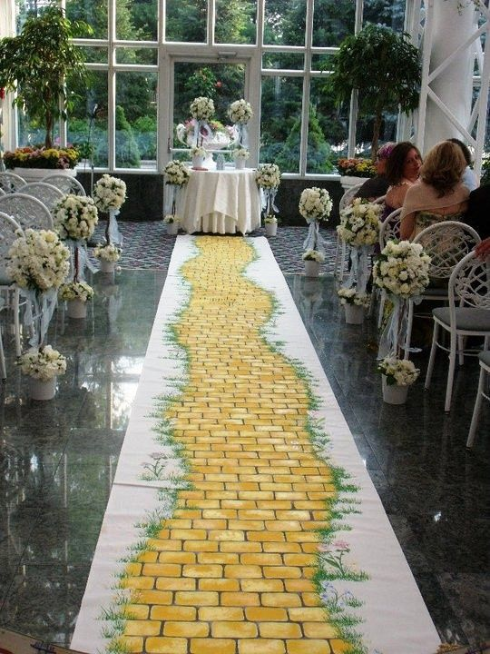 yellow brick road wedding ceremony | Rainbow poof altar with oragami over a yellow brick road aisle runner ...
