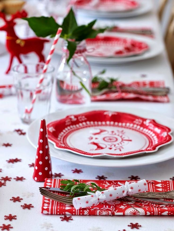 décoration de table de Noël de style scandinave - nappe blanche décorée de mini-flocons de neige, vaisselle en blanc et rouge, serviettes rouges à motifs blancs et papillotes de Noël