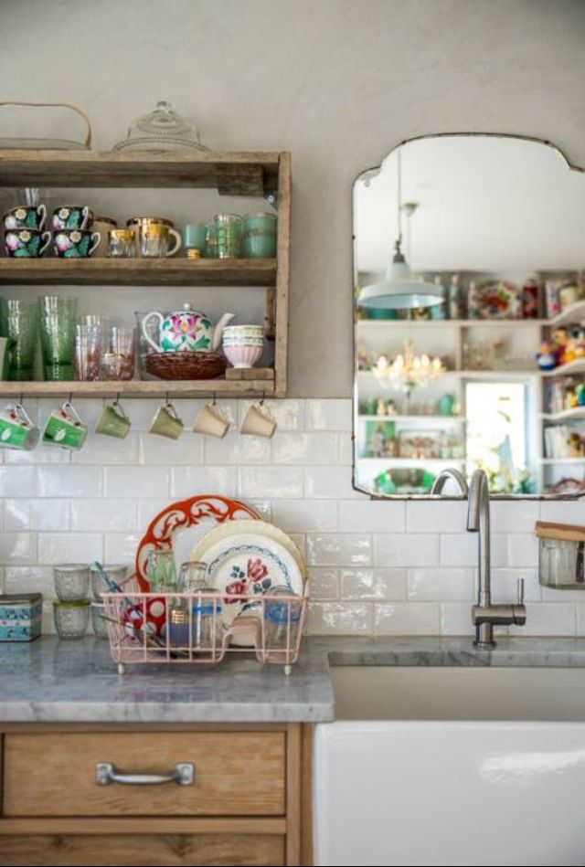 Kitchen filled with a beautiful collection of dishes and cups, vintage mirror over the apron front sink