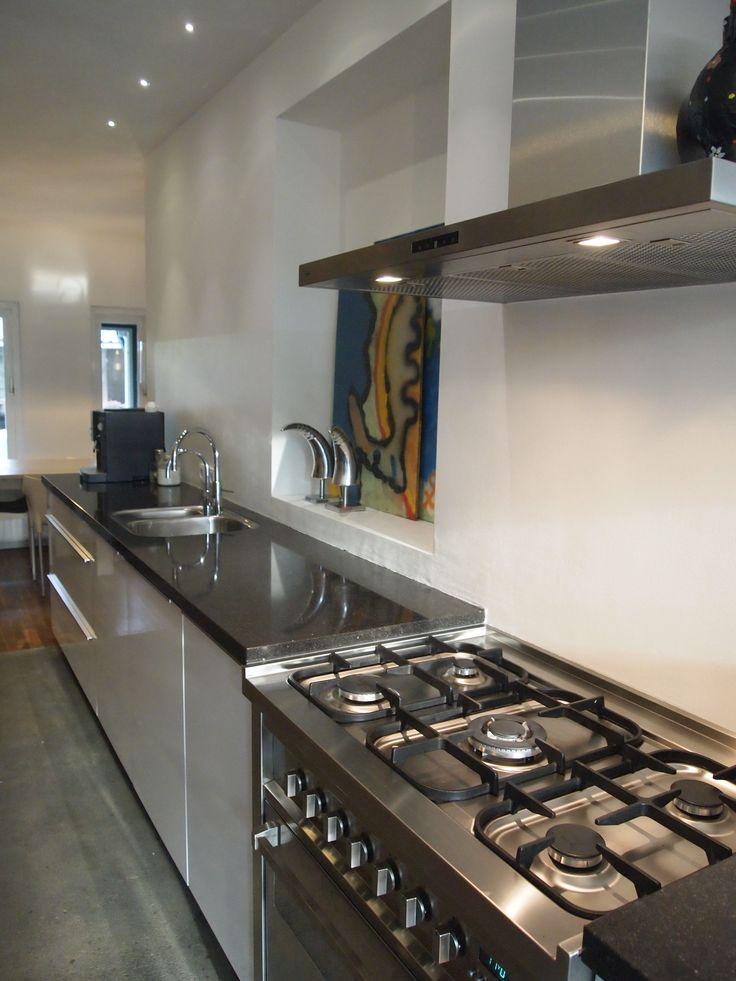 Puurbinnen. Ontwerp keuken. Stoer aanrecht. Hoogglans wit met hardsteen blad en RVS boretti fornuis en oven. Het oude keukenraam is uitgespaard. De vloer is een eenvoudige cementdekvloer behandeld met oxaanolie. Prachtig en puur.