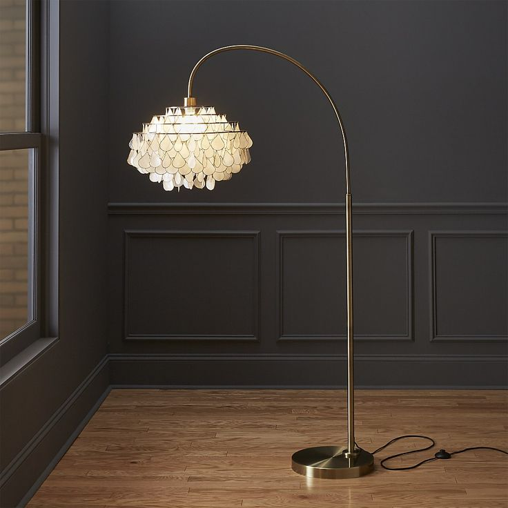 Shop teardrops arc floor lamp.   A simple brass base grounds a wide sweeping arc, culminating in a cascade of iridescent capiz.  Handcrafted by artisans in the Philippines where capiz is abundant, the shells are harvested from local windowpane oysters.