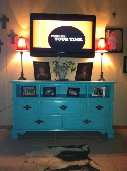 Turn an old dresser into an entertainment center. Found this one for $30. Painted it and left out top drawers for shelving :)