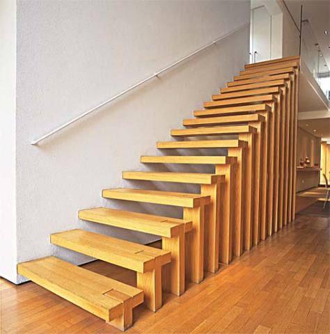 128Esta escada é toda de pranchas de carvalho, com 7 cm de espessura e 1 m de largura cada uma. Os suportes laterais, com 15 cm de largura, estão encaixados nos degraus e fixados com pinos de ferro, semelhantes aos que mantêm a estrutura presa à parede. O corrimão de metal fica quase imperceptível perto da escada escultural. Projeto de Arthur Casas.     Um pedaço de ferro com 15 cm de largura e 7,5 cm de espessura prende cada um...     Os degraus desta escada formam um belo ziguezague na…