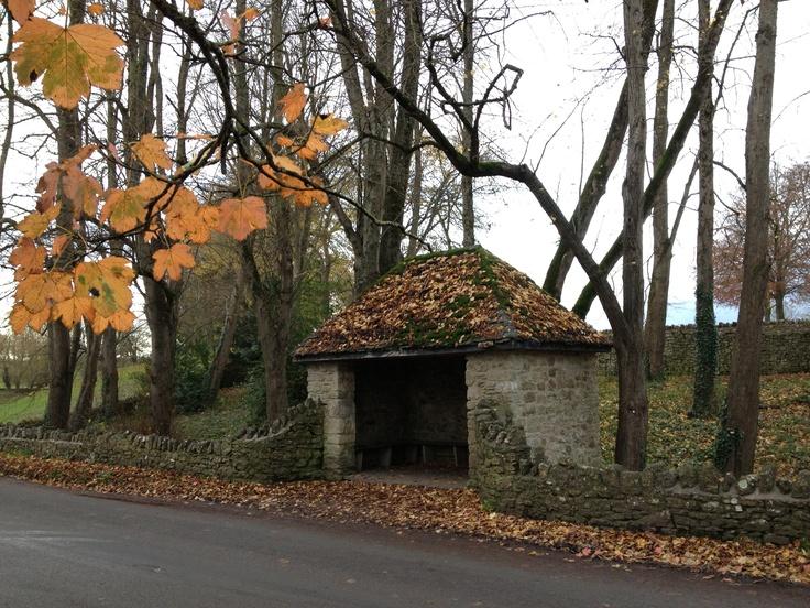 Stone-built, stone-tiled bus shelter.  Mells, Somerset, Autumn 2012