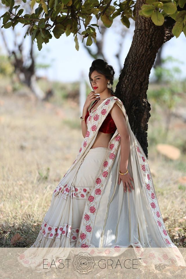 Featured here is the exquisite Camellia design, a cream silk georgette saree with gold-bordered pearl strings on the pallu and resplendent red Camellia embroidered silk trimmings. The wrap is elegantly decorated with floral vines and large, gold-bordered pearls on pleats towards the bottom. Please visit our website at www.eastandgrace.com