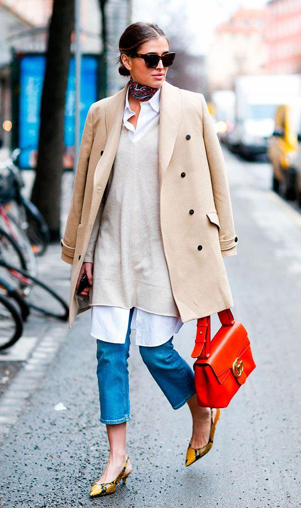 Street style look com casaco bege, camisa branca, e calça jeans.