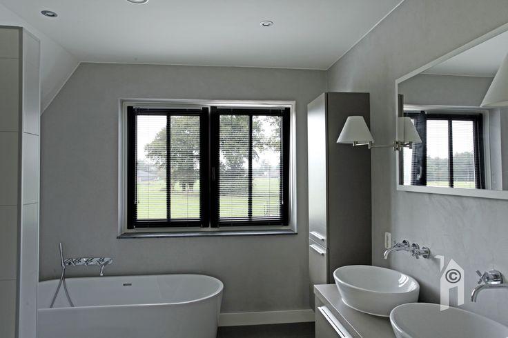 De badkamer heeft 'béton ciré' stucwerk. Het geeft deze natte ruimte een bijzonder karakter.