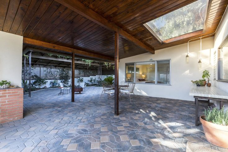 Tagged: Outdoor, Large Patio, Porch, Deck, Hanging Lighting, Pavers Patio, Porch, Deck, and Planters Patio, Porch, Deck. Photo 10 of 15 in A Renovated Midcentury Home in L.A. With Timeless Details Asks $1.3M