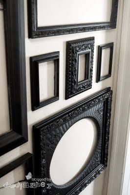 ornate victorian black picture frames on white wall.  I like this for the foyer area and the use of empty frames.