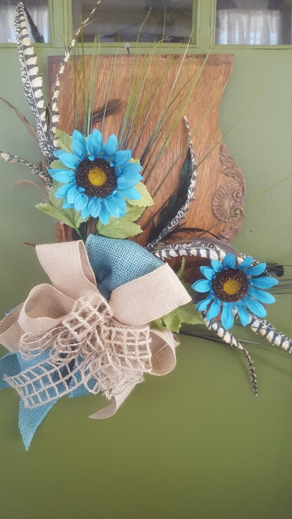 Beautiful Arrangement with Aqua Blue Sunflowers with Feathers for Front Door Hanging or Wall Decor made on an Oak Antique Sewing Machine Door, Actual sewing machine door size is 16 by 11. Overall size with floral and bow added is 19 by 26 by 5 high. The arrangement has Aqua Blue Sunflowers and greenery and feathers and a beautiful Aqua and Tan Burlap Bow to make a nice accent. Please call with any questions. This is handmade and unique to any other floral arrangement I have made. If you have…