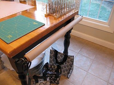 curtain rod hung on end of table for roll of paper or fusible web