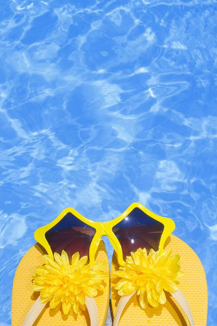 Flip flops and sunglasses by a blue pool