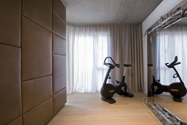 Fitnesseck mit edler Lederwand und großem Spiegel