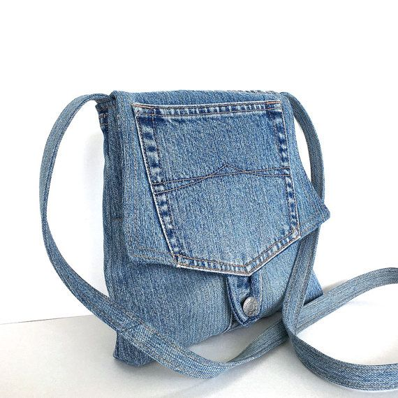 I constructed this cute small messenger bag from recycled blue denim pant. It has an A-shape body,and features a flap, decorated with an original pocket.It also has one outside pocket on the backside. I lined it with a polyester print fabric , and aadded one inside pocket . A loop and metal botton keep the bag closed. This small messenger bag can accompany you on many different adventures. Measurements: width: 7 to 9 height: 8.5 depth: 1 strap: 47
