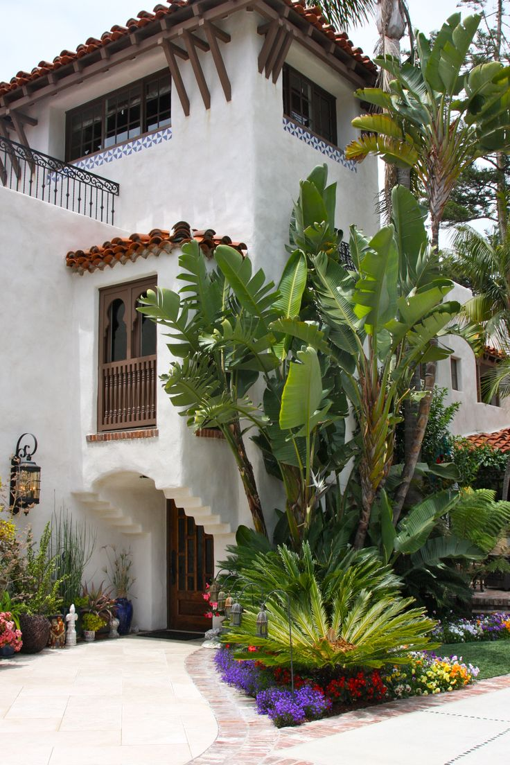 Old California and Spanish Revival Style Home with tropical plantings. White…