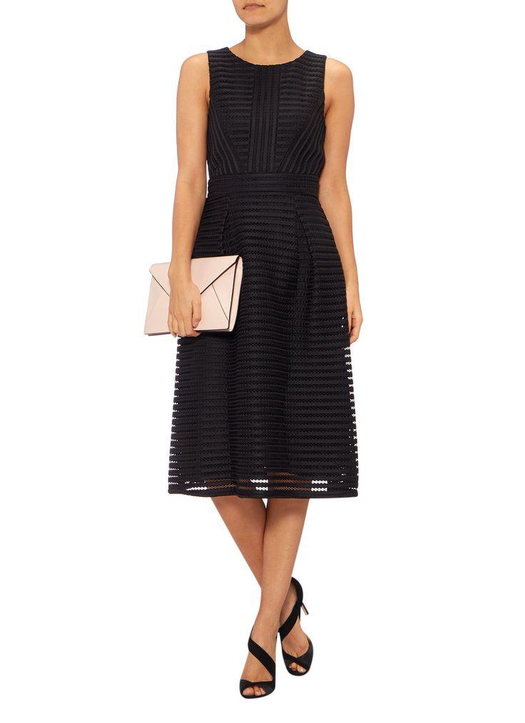 Deze zwarte A-lijn jurk kenmerkt zich door de gestreepte textuur en de verfijnde kanten overlay. Het mouwloze model heeft een hooggesloten ronde halslijn en is aan de achterzijde uitgerust met een ritssluiting. Voorzien van een volledige voering voor een comfortabele pasvorm.