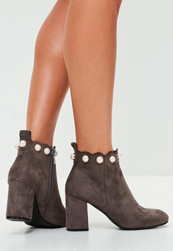 These ankle boots feature a faux suede fabric, gray hue and a contrasting pearl details to the top.