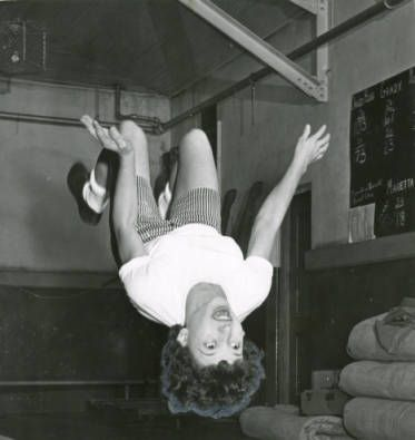 "1958, ""Becky Butler Goes Head Over Heels: Girls Invade YMCA for Gymnastics Classes."" AJCP552-056a, Atlanta Journal Constitution Photographic Archives. Special Collections and Archives, Georgia State University Library."
