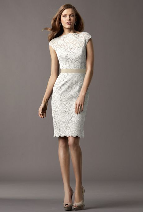 Brides: Encore by Watters. Ivory lace bateau neckline with a covered back and cap sleeves with slim above the knee length skirt and grograin sash at waist.