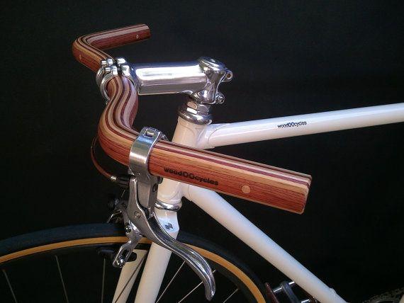 Manubrio della bicicletta baffi che combina due tipi di legno: Legno bubinga, quercia e frassino Finito con un sottile strato di vernice poliuretanica. Rinforzato con due tasselli in alluminio nella zona di staminali. Logo impresso. * * per ahead steli * *. Diametro gambo: 25,4 mm Lunghezza: 49 cm Diametro: 25,4 mm Peso: 240g. Sweep: 50 gradi  Il nostro manubrio baffi si ispira molto popolare Nitto B2522AA SSB progettato dal leggendario Hiroshi Iimura di Jitensha Studio a Berkeley CA…