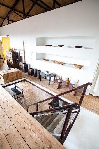 室内で使われている階段は、以前に屋外で使われていたもの。使い込まれた鉄の深い味わいが、高山さんの家具にもよく似合う。パーティションの奥が寝室になっている。棚には益子の陶芸作家の作品と、高山さんの作品が並ぶ。「手前のテーブルは実家にあった漆塗りのものです」
