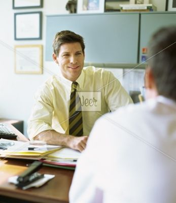 side view of two mid adult men talking Stock Photo