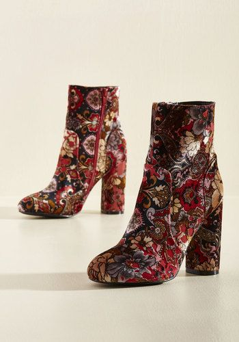 Go ahead, look twice - there's more to these red velvet booties than meets the eye! Not only does this block-heeled pair feature a grey, black, pink, and yellow floral pattern, but it also flaunts clean tailored lines, making for a most entertaining reason to double-take.