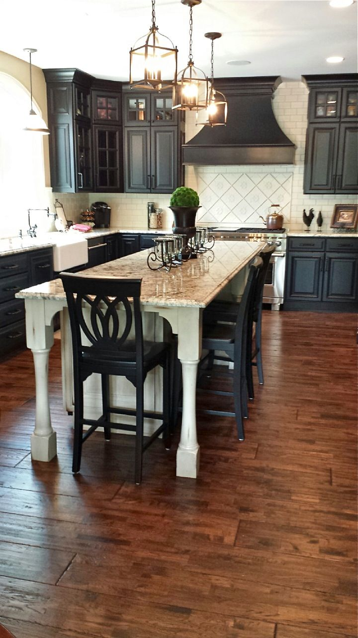 Kitchen with Black Cabinets. Black and white kitchen with white tile, wood flooring, granite countertops, white sink, professional oven range and center island.