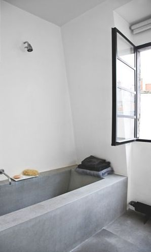 Another concrete look bath. I like the idea of the shower head in the middle of the bath rather than the end