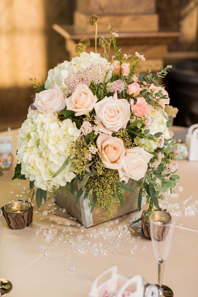 Centro de mesa rustico con base cuadrada de madera y flores de colores blush. #BodasRusticas
