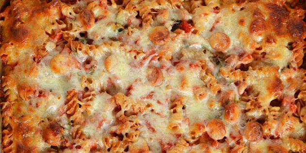 Skøn opskrift på pastagratin med pølser, løg og peberfrugt samt hakket tomat og smeltet ost på toppen.