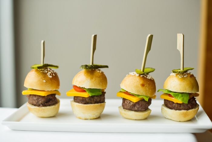 Miniature beef burgers, topped with melted cheddar cheese, dill pickles, and butter lettuce, on petite sesame-seed brioche buns, by L-Eat Catering in Toronto  Photo: Emma McIntyre for BizBash
