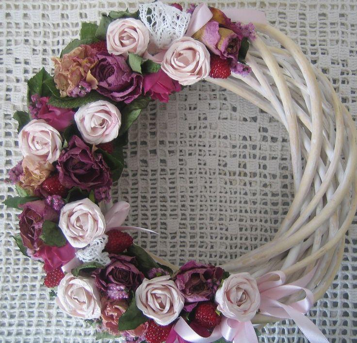 Růžová zahrádka Věnec na proutěném základu o průměru cca 26cm. Použila jsem sušené a papírové růže, umělé maliny, krajkua stuhy. Slouží jako dekorace.
