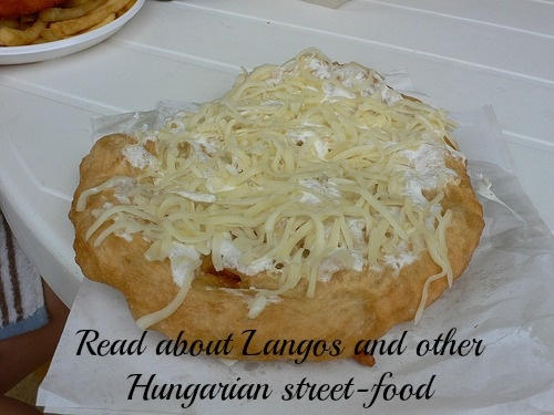 Click to read about Lángos, a cross between a dougnut and a pancake that is traditionally served with cream cheese and grated cheese on top, as well as plenty of other sweet and savoury toppings. #Budapest #Hungary #food #streetfood #travel