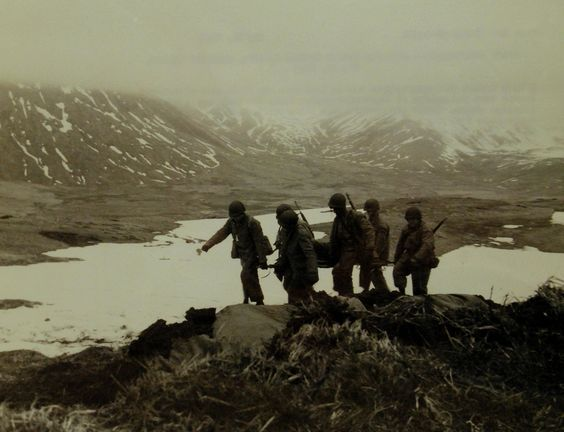 Lot-803-35: Aleutian Islands Campaign, June 1942 - August 1943. Allied Landing on Attu Island, May 11 1943. From an advanced command post, a detail of soldiers carry back a wounded comrade. The photograph reveals the rough terrain in which the fighting for Attu took place. Japanese snipers generally kept just above the fog line. U.S. Navy photograph, released May 26, 1943. Photographed through Mylar sleeve.