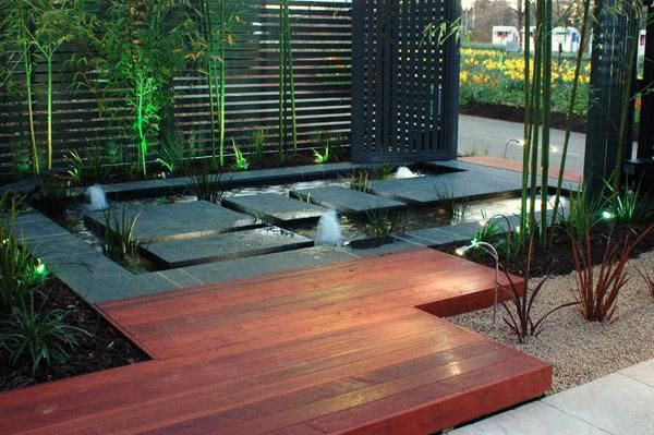Ground level deck with privacy screen and water feature for Back garden designs australia