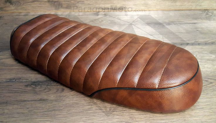 Description: This is an excellent vintage Cafe Racer motorcycle seat. It's durable, waterproof, and made from high quality leatherette with a beautiful leather coloring. The addition of a Flat Brat st