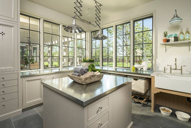 Laundry room. Laundry Room. Laundry Room with pale gray cabinets, pale gray island with stainless steel countertop. A washstand features a farmhouse sink with marble backsplash. #Laundryroom #Laundryrooms #Laundryroom