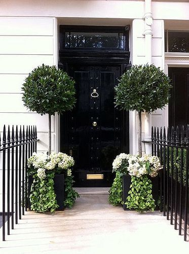 Love the glossy black door – and the planters with bay lead topiaries, white flowers, and trailing greenery are the perfect counterbalance to the door.