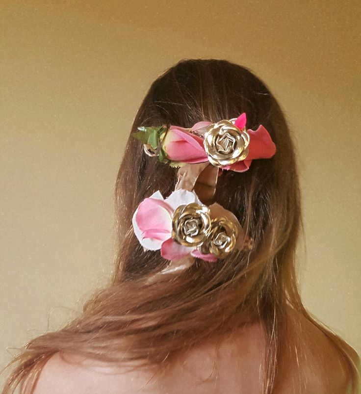 Metallic roses and pink petal barrettes tucked into the hair.