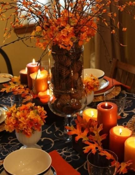 DIY Centerpiece using pinecones in a large glass jar accented w/ glowing candles and orange hydrangeas