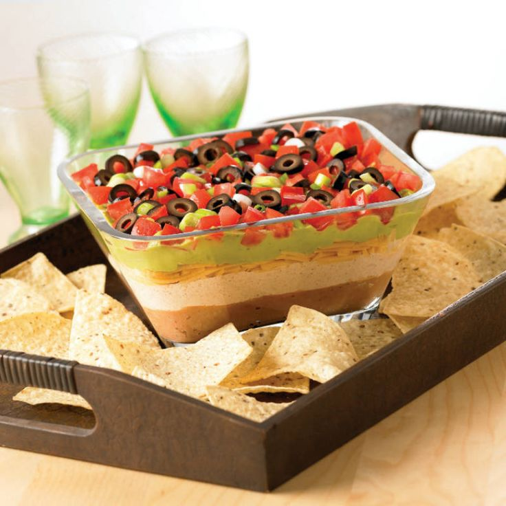 Refried beans, cheddar cheese, guacamole, tomatoes and more! Everyone will want to dig into this spicy layered dip... bring on the chips!
