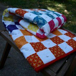 Externality Tied Scrap #Quilt #tutorial by Shana from Needyl. This easy scrap quilt pattern is a great way to use up leftover fabrics from other quilts. It has the look of traditional baby quilts since it is tied, rather than quilted, in the center of each white square.
