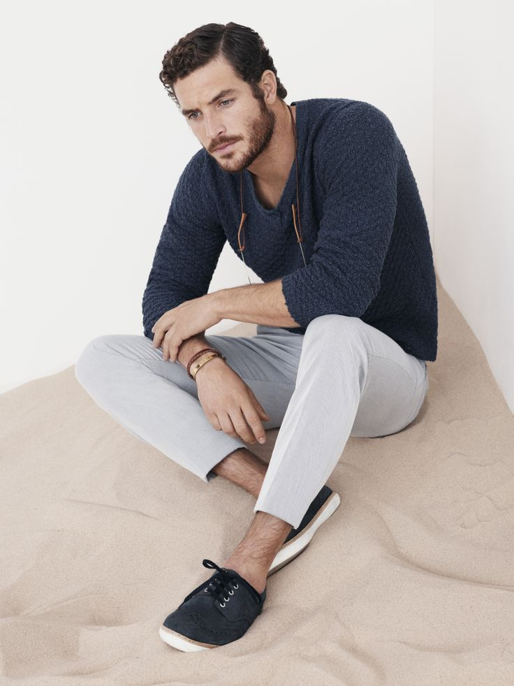 Shop this look on Lookastic:  http://lookastic.com/men/looks/navy-v-neck-sweater-grey-chinos-black-low-top-sneakers/7032  — Navy V-neck Sweater  — Grey Chinos  — Black Low Top Sneakers